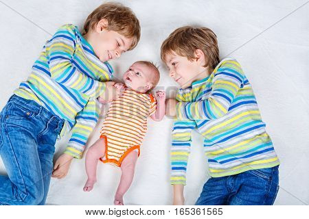 Two happy little preschool kids boys with newborn baby girl, cute sister. Siblings, , twins children and baby playing together. Kids bonding. Family of three, love.