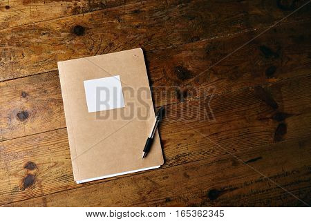 Unlabeled craft notebook and a plastic black pen on an old textured wooden table