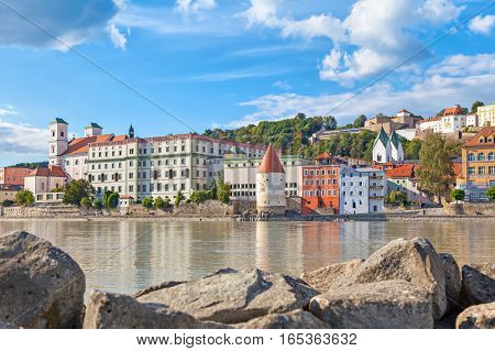 Buildings and Schaibling Tower on the side of Inn river near its confluence with Danube in Passau Bavaria Germany