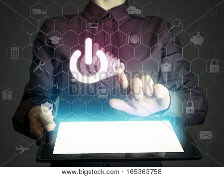 Image of a person with tablet in her hands. Finger touches the power button icon. ON- OFF concept of something.