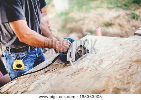Industrial Worker Using Circular Saw On Wooden Board In Carpentry Workshop