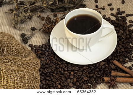 White cup of coffee to wake up with a bag of coffee beans and cinnamon