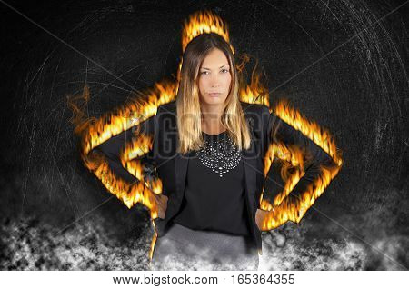 Female boss woman burning with rage. Very angry with fire flames and smoke. A fiery woman has her fists on her hips with an aggressive attitude. Black painted wall background with scratches.