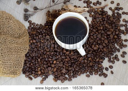 White cup of coffee standing on coffee beans poured out of the bag on a gray tablecloth
