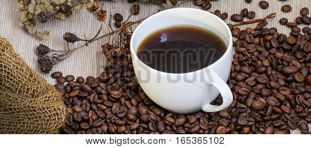 cup of coffee coffee beans bag on a wood table on a black background