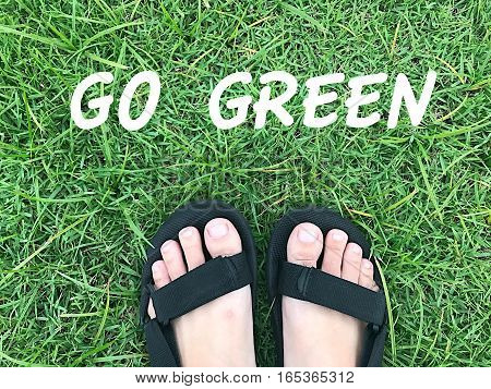 foot on green grass with go green word