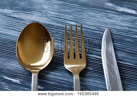 Gold spoon fork and knife on gray wooden background. retro style kitchen tableware with scratches and scrapes. Soft focus. macro