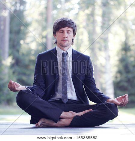 Businessman in suit practicing yoga in park