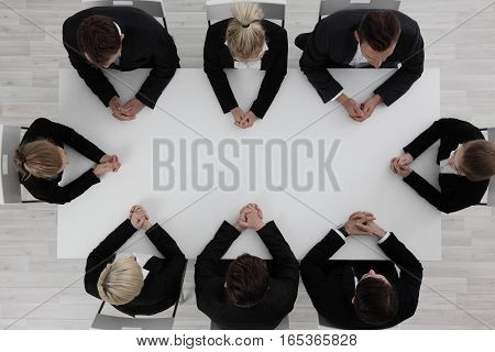 Business people team sitting around empty table top view
