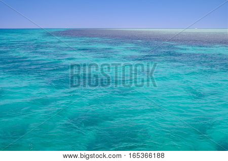 Red Sea background, clean blue water, small waves, coral reef