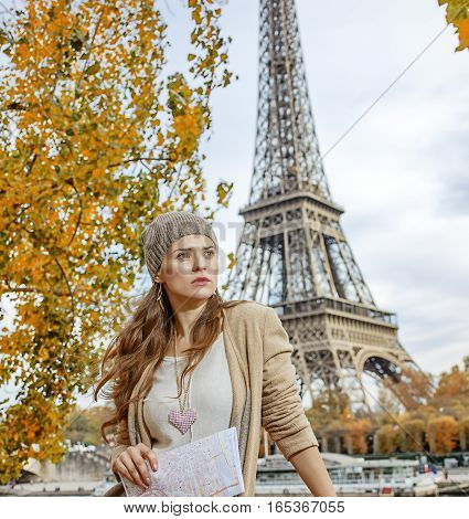 Autumn getaways in Paris. young elegant woman on embankment in Paris France with map looking into the distance