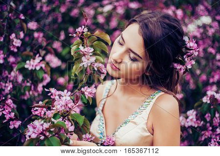 Portrait of young beautiful woman posing among blooming apple trees. Closed Eyes. Professional make-up and hairstyle. Perfect skin. Fashion photo. Natural beauty. Springtime.