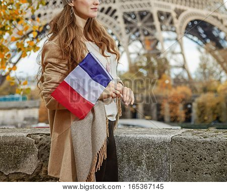 Autumn getaways in Paris. happy young elegant woman on embankment near Eiffel tower in Paris France with flag