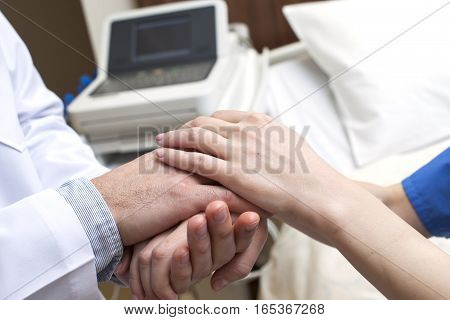 Close-up of doctor holding patient's hands in hospital.