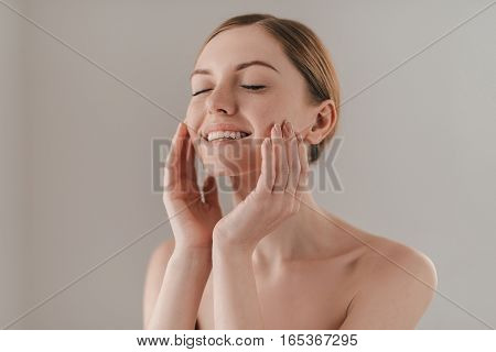 Enjoying the softness of her skin. Studio portrait of attractive woman with freckles on face touching her skin and keeping eyes closed while standing against background poster