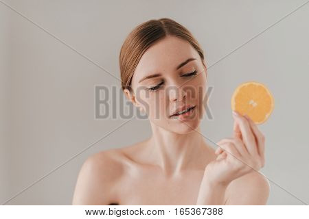Fresh fruits make your skin perfect. Attractive young woman holding orange slice and looking away while standing against background