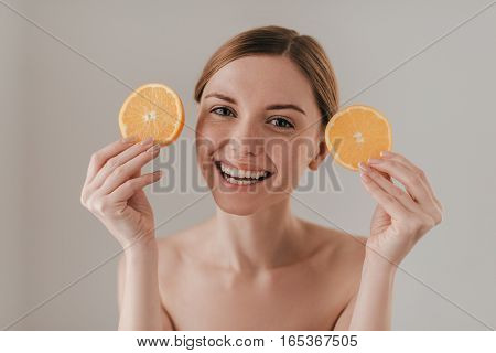 Using fruits for skin care. Beautiful young woman holding orange slice and looking at camera while standing against background