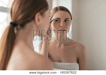 Beauty treatment. Over the shoulder view of attractive young woman plucking her eyebrows while standing in front of the mirror