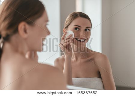 Good care of her skin. Over the shoulder view of young woman cleansing her skin with a cotton pad while looking in the mirror
