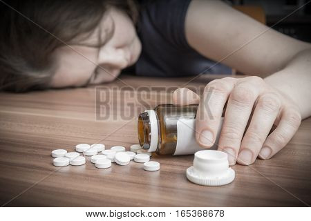 Young Woman Commiting Suicide By Overdose Of Pills.