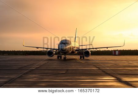 Large commercial aircraft on the runway during sunset. Concept of travel around the world.
