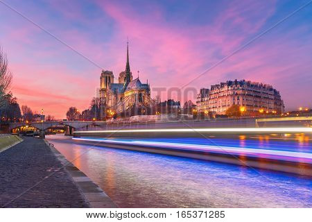 Picturesque grandiose sunset over Cathedral of Notre Dame de Paris and luminous track from the boat, France
