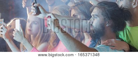 People recording the concert using their smartphones
