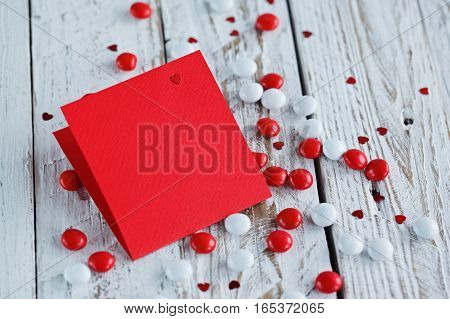 Valentine's day card with small hearts and red white candy on light wooden background.