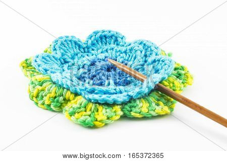 Crochet hook and flower on white background