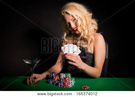 Happy and lucky woman playing poker by the poker table