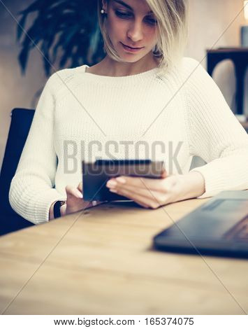 Young businesswoman using digital tablet at modern working place.Concept of coworking people work with mobile devices.Vertical, blurred background.Film effect