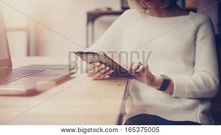 Concept of searching for new business solution.Pensive young beautiful businesswoman using tablet while sitting at her working place.Horizontal, blurred background.Flare effect