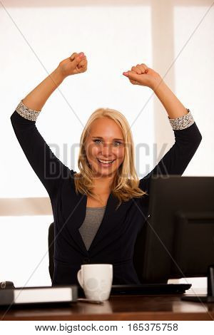 Business Success - Woman Celebrating A Victory Or Triumph Behind The Desk In Office After Acheaving
