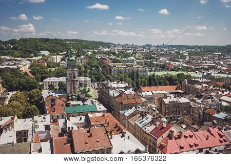 Blue cloudy sky and town. Trees and buildings. Townscape at daytime.