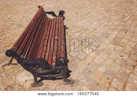 Bench on pavement background. Wooden and iron bench. Sit back and relax.