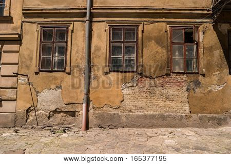 Wall of damaged building. Old dirty windows. Abandoned and forgotten.
