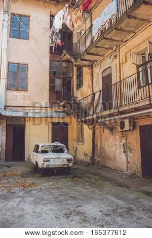 Old town building. Part of deconstructed car. Life in poor district.
