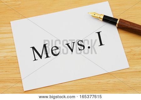 Learning to use proper grammar A white card on a desk with a pen with words Me vs I