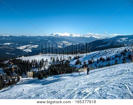 View from the high to the ski resort which attracts skiers on the ski slopes the snow-capped mountain peaks snowy trail a steep ski