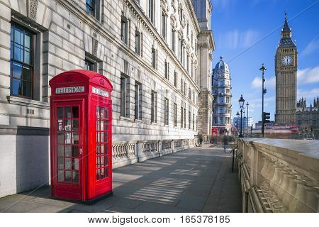 London England - Traditional red british telephone box with Big Ben and Double Decker bus at the background on a sunny afternoon with blue sky and clouds