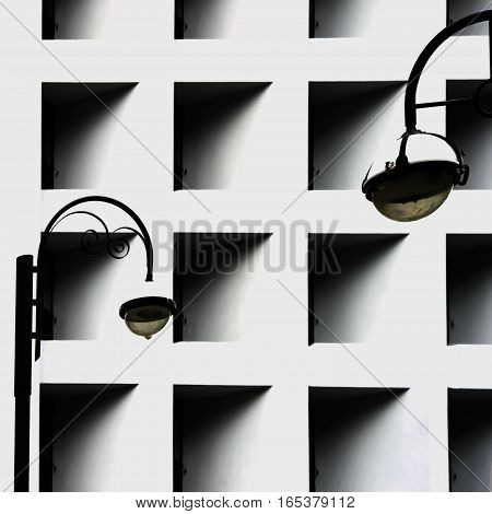 Geometric abstract in real black and white color, Street Lights and Facade of the building with windows, lines and shadows close up, modern street background