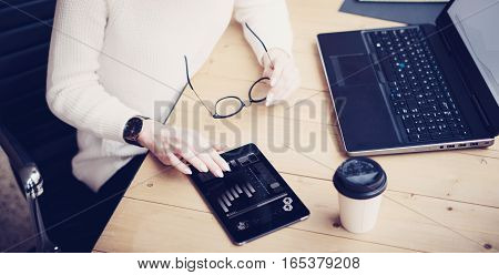 Top view of young beautiful woman working at the wooden table with mobile devices.Female hand touching digital tablet, graph and diagram on display.Horizontal wide, blurred background