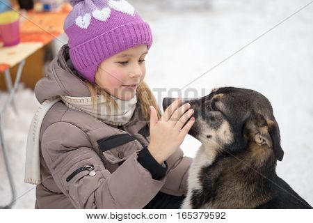 Gomel, Belarus - January 15, 2017: Friendship With Animals. Girl Regrets Stray Dog In Winter.