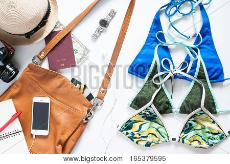 Flat lay set of summer items. Three summer colorful bikini with mobile phone and items for summer vacation on white background