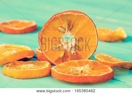 Slices of dried orange on the old wooden background. Close-up.