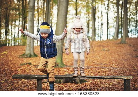 Two Children Jumping From Bench In Forest