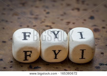 Fyi (for Your Information) Text On Wooden Cubes On A Brown Cork Background