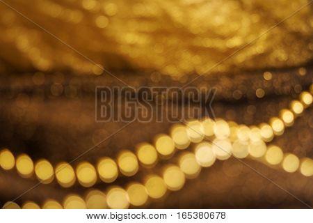 Brown gold glittering Defocused abstract holidays lights on dark background. Golden Festive Christmas background. Abstract twinkled bright background with bokeh defocused gold color lights.