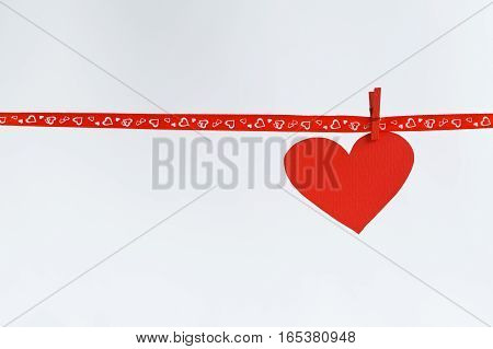 Red Paper heart hanging on red ribbon on white background. Concept Valentines day