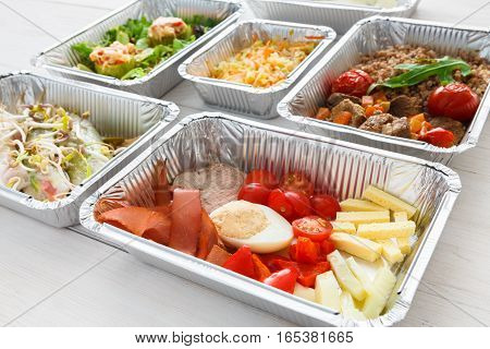 Healthy food in foil boxes. Meat with egg and vegetables, cherry tomatoes and beef. Restaurant dishes delivery, lunch for diet, daily ration